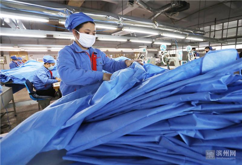2月10日,邹平市魏桥创业集团的向尚服饰公司工人在整理生产好的防护服,其布料来源于当地企业。该公司于当日紧急转产,支援疫情防控。