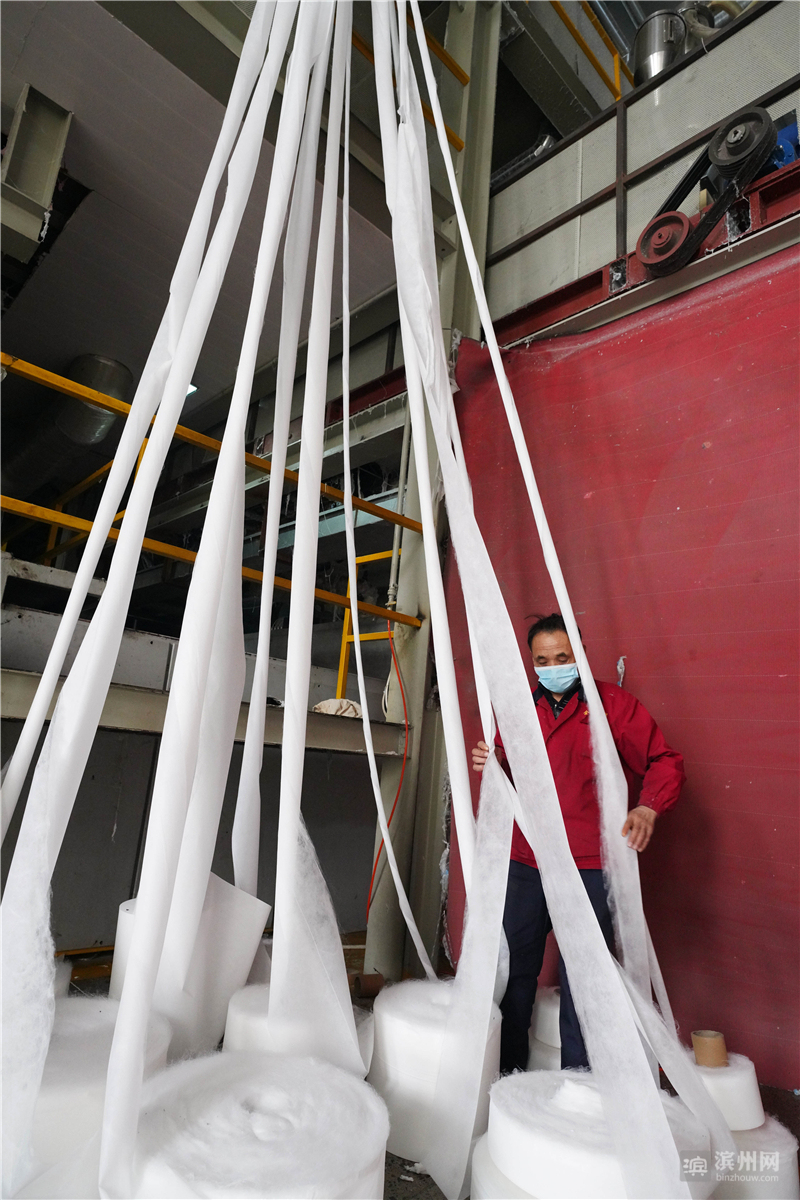 2月11日,邹平市好生街道金信无纺布工厂工人在无纺布生产线上忙碌。该厂日生产布料20吨。
