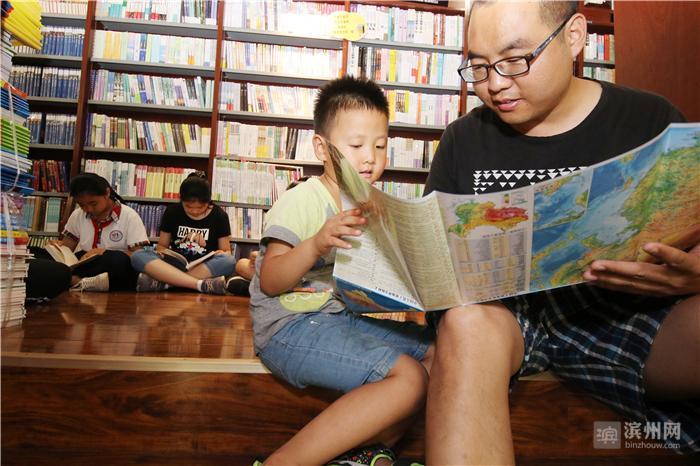 7月13日,山东省无棣县新华书店,一位家长在教孩子识世界地图。