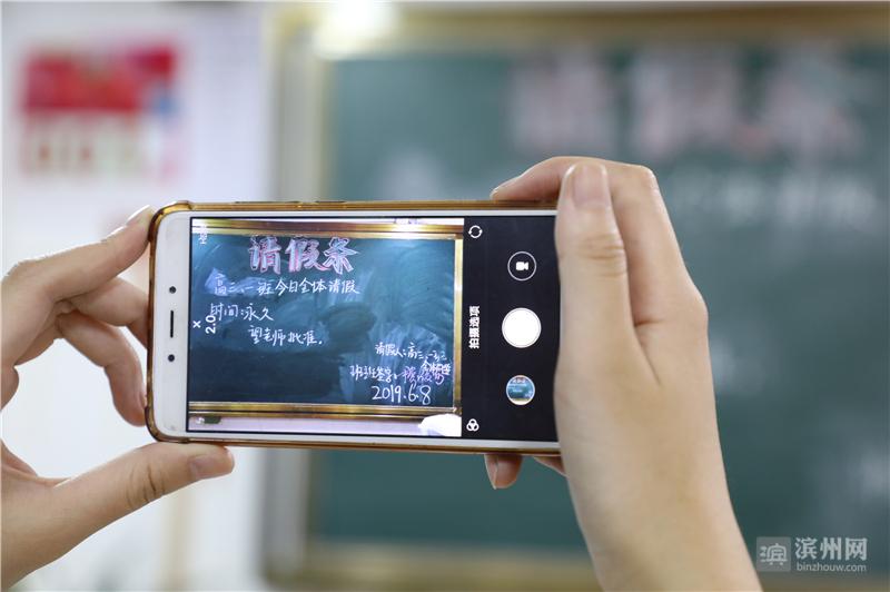 """一名同学用手机拍摄下""""离别班会""""黑板上的""""集体请假条""""留作纪念。"""