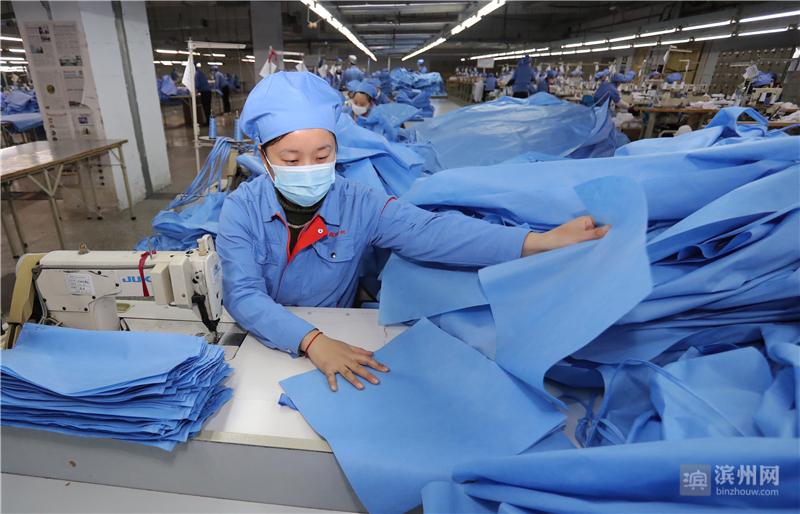 2月10日,邹平市魏桥创业集团的向尚服饰公司工人在生产防护服,其布料来源于当地企业。该公司于当日紧急转产,支援疫情防控。