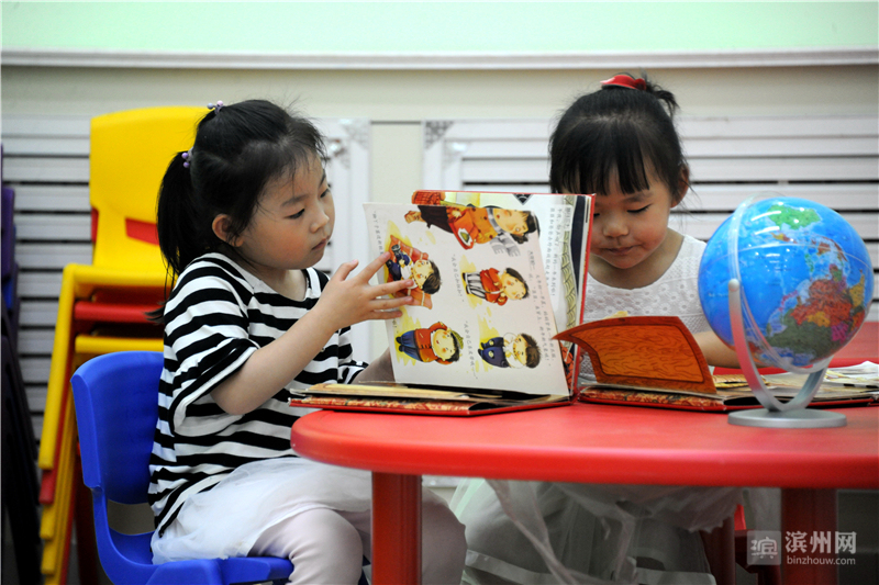 小娃娃在读书馆(室)阅读画册、