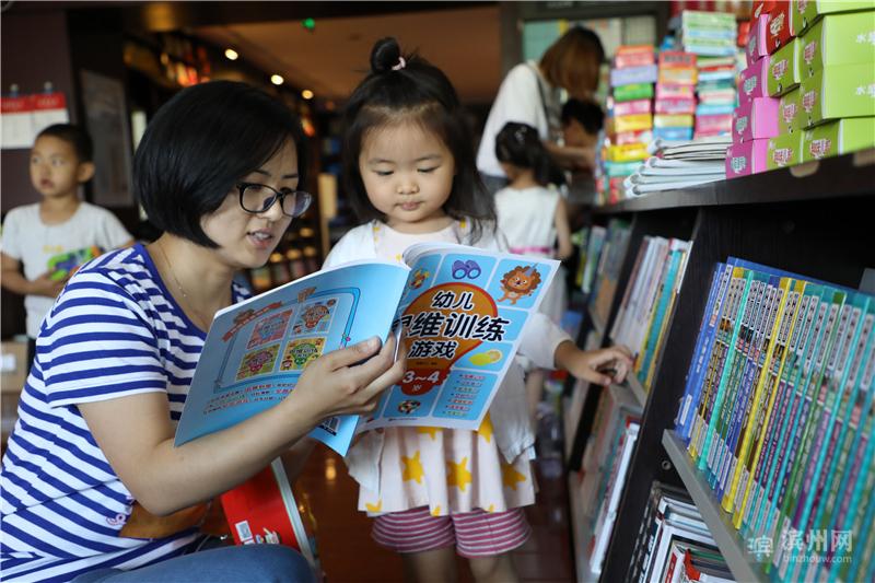 6月9日,在博兴县新华书店,一名年轻妈妈和孩子在一起阅读图书。