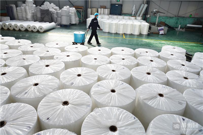 2月11日,邹平市好生街道华强无纺布工厂工人把打包好的无纺布用小拖车运走。该厂日生产布料10多吨。