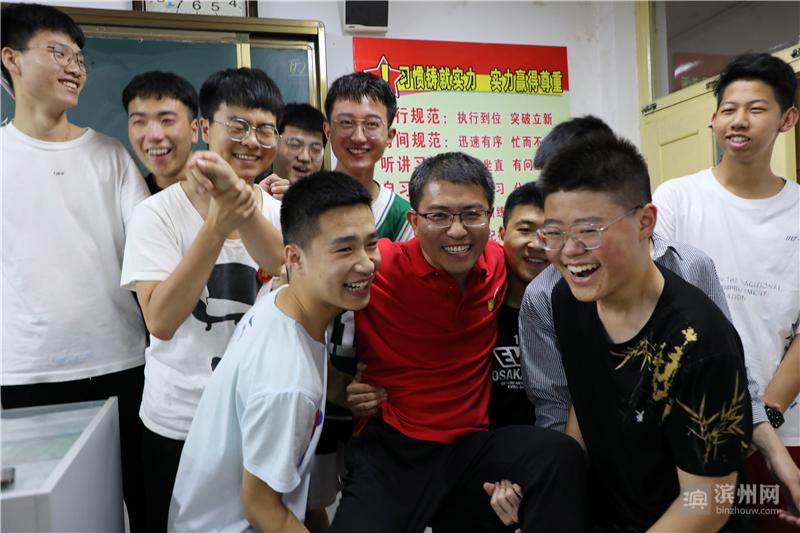 班主任穆俊洲被几名男同学抬起来。
