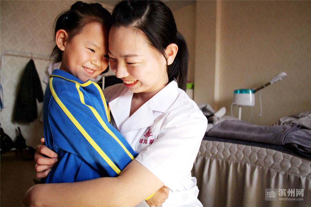 在一家美容机构工作的张文利与女儿王雨霏拥抱。