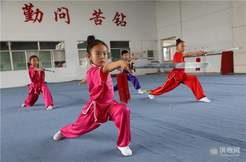 7月11日,在博兴县体育中学武术训练馆,小学生在练习武术。